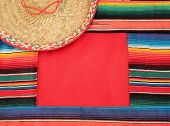foto of mexican fiesta  - Traditional Mexican fiesta poncho rug in bright colors with sombrero background with copy space - JPG