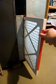 stock photo of furnace  - Close up of hand changing home furnace filter - JPG