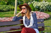 picture of sitting a bench  - Pensive girl sitting on a park bench wearing a brown hat - JPG