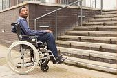 image of staircases  - young man in a wheelchair waiting for help at the bottom of a staircase - JPG