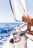 picture of rope pulling  - Handsome man working on sailboat - JPG