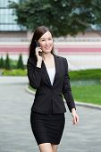 image of girl walking away  - Businesswoman walking on the street and talking to cellphone - JPG