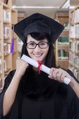 foto of graduation  - Happy female graduate student wearing graduation hat and gown standing in the library while holding a diploma - JPG
