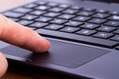 pic of touching  - Index finger touching touch pad on laptop keyboard - JPG