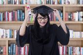 stock photo of graduation  - Female bachelor holding a diploma while wearing graduation gown and celebrate her graduation in library - JPG