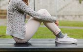 picture of sitting a bench  - Closeup of beautiful young trendy woman sitting with her legs up on a park bench - JPG