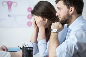 picture of cry  - Crying young woman sitting with husband at gynecologist office  - JPG