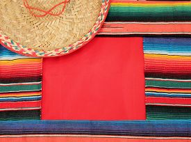 image of mexican fiesta  - Traditional Mexican fiesta poncho rug in bright colors with sombrero background with copy space - JPG