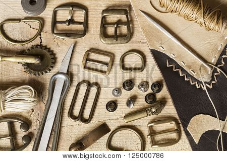 Leather craft toolsthread and buckles on a wooden background