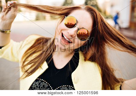 close-up lifestyle portrait of young girl having fun at cool sunset. Travel concept, happy girl make picture and having fun, laughing and make funny face on camera, sunshine girl