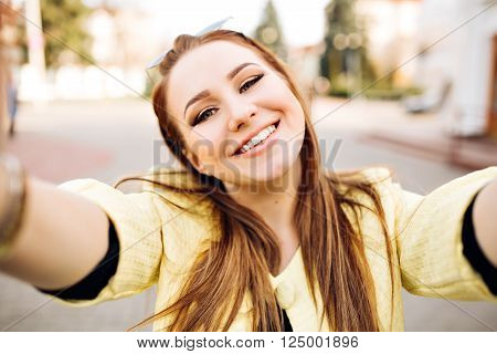 Close up lifestyle portrait of cheerful hipster girl going crazy making funny face. Bright colors, urban street background.accessories