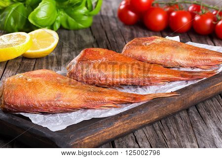 Red Sea Bass on a parchment paper on an old wooden table with basil leaves lemon slices and cherry tomatoes on the background horizontal close-up