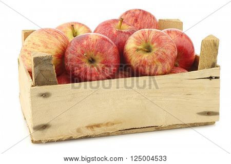 fresh sweet small apples in a wooden crate on a white background