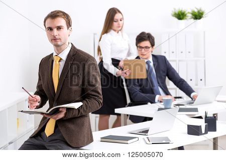 Businessman making notes in book businesswoman showing documents to businessman at background. Office. Concept of work.