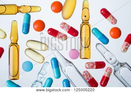 Many ampoules of different types and colours coloured pills. Concept of medicine.