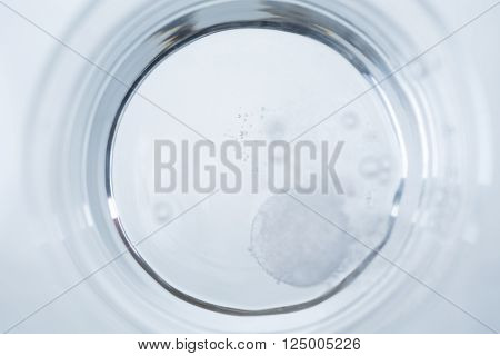 Topview of water glass with dissolving tablet