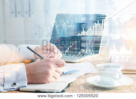 Businessman drawing graphs in copybook. Double exposure