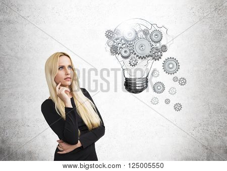Idea concept with pretty businesswoman and lightbulb and gear sketch on concrete wall