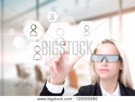 Businesswoman in 3D glasses touching virtual screen hexagonals with people models on it. Office at background. Concept of 3D glasses.