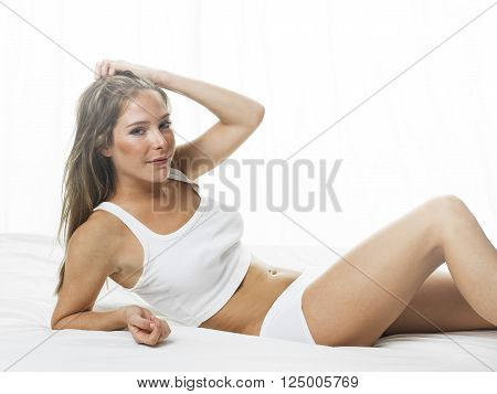 beautiful woman laying on the bed in the morning