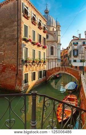 Colorful narrow lateral canal, church Santa Maria dei Miracoli and pedestrian bridge in the sestiere of Cannaregio at morning, in Venice, Italia