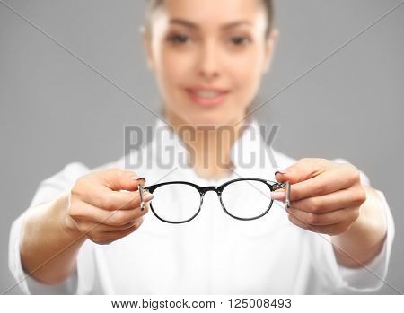 Young female doctor giving glasses on grey background