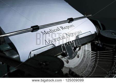 Old typewriter and inserted white sheet of paper with medical report on anorexia