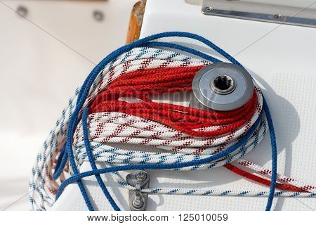 Detail of a sailboat deck with a winch and nylon ropes