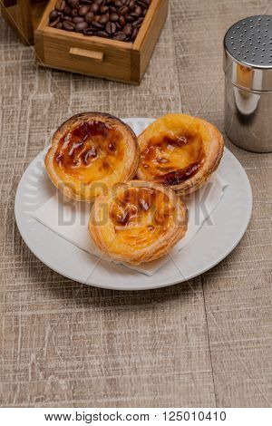 Pasteis de Nata or Portuguese Custard Tarts on wooden table.