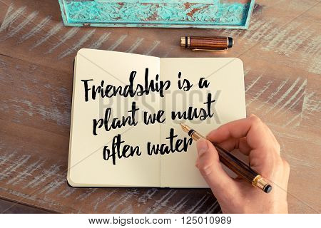 Retro effect and toned image of a woman hand writing on a notebook. Handwritten quote Friendship is a plant we must often water as inspirational concept image