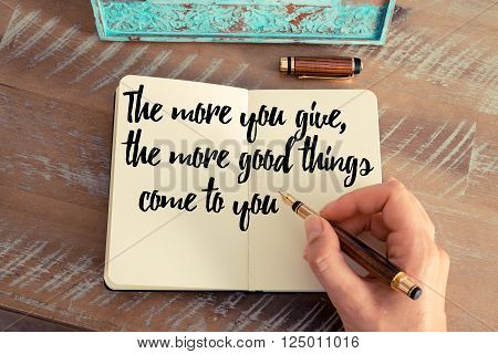 Retro effect and toned image of a woman hand writing on a notebook. Handwritten quote The more you give, the more good things come to you as inspirational concept image