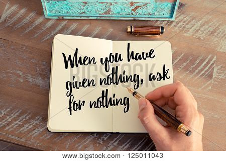 Retro effect and toned image of a woman hand writing on a notebook. Handwritten quote When you have given nothing, ask for nothing as inspirational concept image