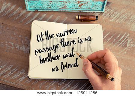 Retro effect and toned image of a woman hand writing on a notebook. Handwritten quote At the narrow passage there is no brother and no friend as inspirational concept image