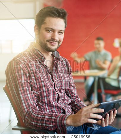 Casual portrait of a millenial business man using technology in a bright and sunny startup with the team in the background