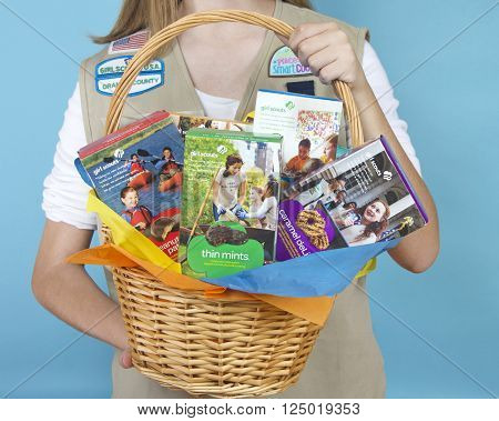 ALAMEDA CA - FEBRUARY 18 2016: Cadette Girl Scout holding Gift Basket with assortment of ABC Baker's brand Girl Scout cookie boxes. Close up on basket in hands. Girl Scout cookies only available once a year.