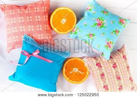 aromatherapy pillows, aromatization space. Four small decorative pillows pale blue and pink with lace. Handmade. Vitamins for a good mood.  White wooden background and orange halves.