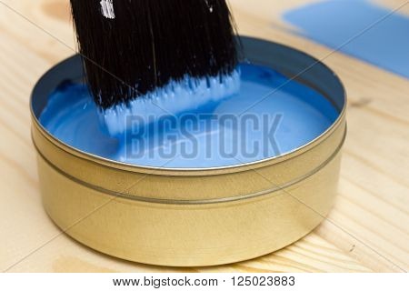 Brush for paint and paint on a wooden background