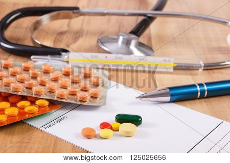 Medical pills tablets or supplements for therapy prescription thermometer and stethoscope on desk in doctor office concept of treatment and health care