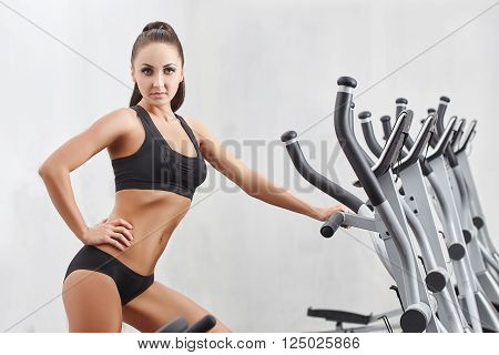Cute female athlete posing with simulators on white
