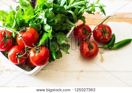 Fresh organic vegetables like a tomatoes, cucumer, green peper, spinach and parsley on rustic wooden background