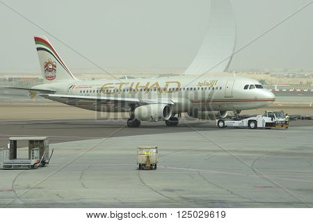 ABU DHABI, UAE - MARCH 10, 2015: Towing aircraft Airbus A320-232 (A6-EIR) Etihad Airways in Abu Dhabi