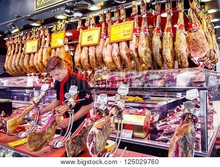 SPAIN, BARCELONA, JUNE, 29, 2015 - Young spanish dealer slicing iberico and serrano jamon, hanging on the La Boqueria Market in Barcelona, Spain.