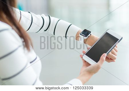Woman using smart watch connecting with cellphone