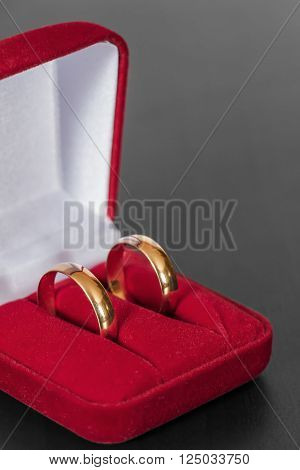 Two wedding rings in a red box lie on the surface of the black table