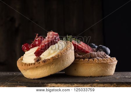 Delicious cupcakes with strawberries redcurrants and blackcurrants on a wooden surface