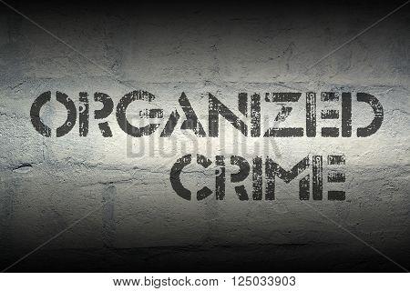 organized crime stencil print on the grunge white brick wall