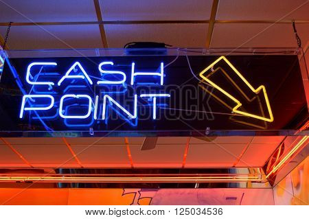 Colourful neon sign cash point with arrow