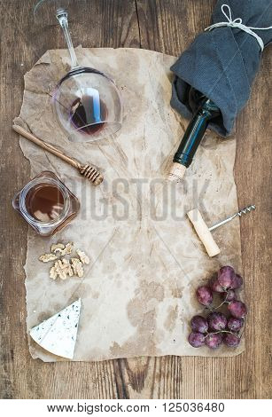 Wine and appetizer set with copy space in center. Glass of red wine, bottle, corkscrewer, blue cheese, grapes, honey and walnuts on oily craft paper over rustic wooden table, top view