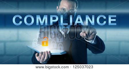 Business manager is touching COMPLIANCE on a virtual interactive screen. Business challenge metaphor and information technology concept for conforming to corporate rules and regulations.