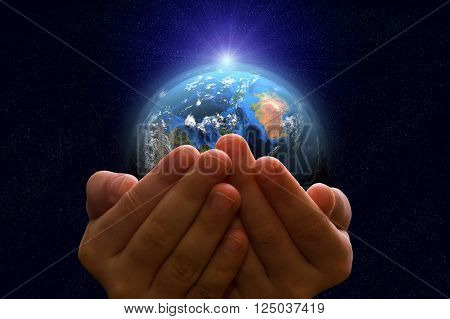 Child holding a glowing earth globe in his hands. Earth image provided by Nasa.